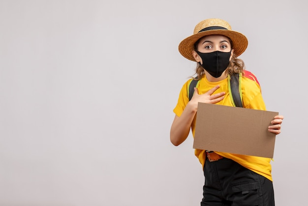 Vorderansicht des weiblichen reisenden mit rucksack, der pappe hält, die hand auf ihrer brust auf grauer wand setzt