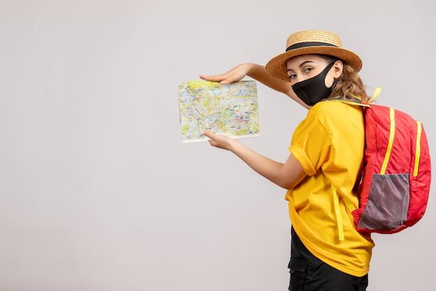 Vorderansicht des weiblichen reisenden mit schwarzer maske, die karte auf weißer wand hält