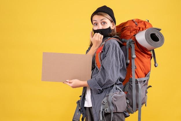 Vorderansicht des weiblichen reisenden mit schwarzer maske und rucksack, die karton auf gelber wand halten