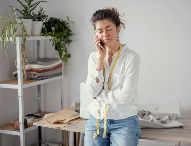 Vorderansicht des weiblichen schneiders, der am telefon spricht