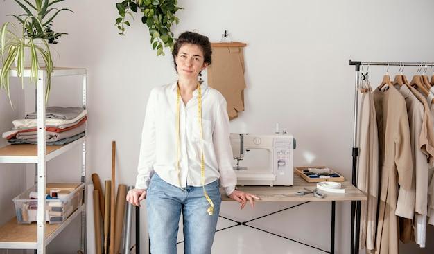 Vorderansicht des weiblichen schneiders, der im studio mit nähmaschine aufwirft