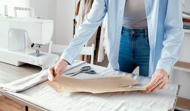 Vorderansicht des weiblichen schneiders, der stoff für kleidungsstücke vorbereitet