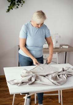 Vorderansicht des weiblichen schneiders im studio, das stoff schneidet