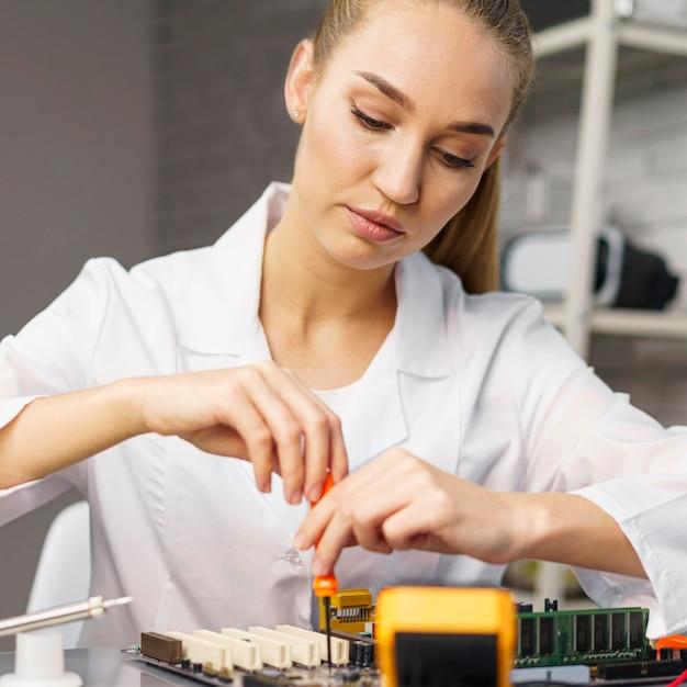 Vorderansicht des weiblichen technikers mit elektronikplatine