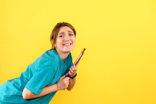Vorderansicht des weiblichen tierarztes, der analysen auf gelber wand hält