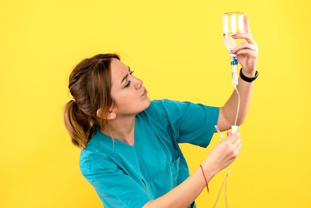 Vorderansicht des weiblichen tierarztes, der tropfer auf gelber wand hält