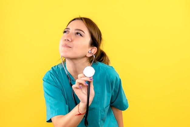 Vorderansicht des weiblichen tierarztes mit stethoskop auf gelber wand