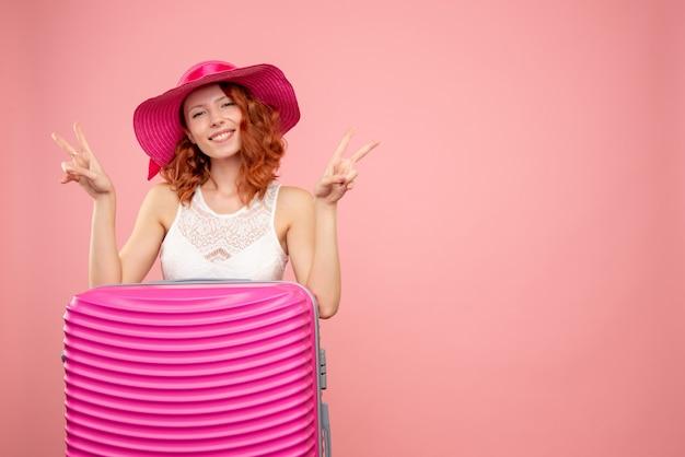 Vorderansicht des weiblichen touristen mit rosa tasche an der rosa wand