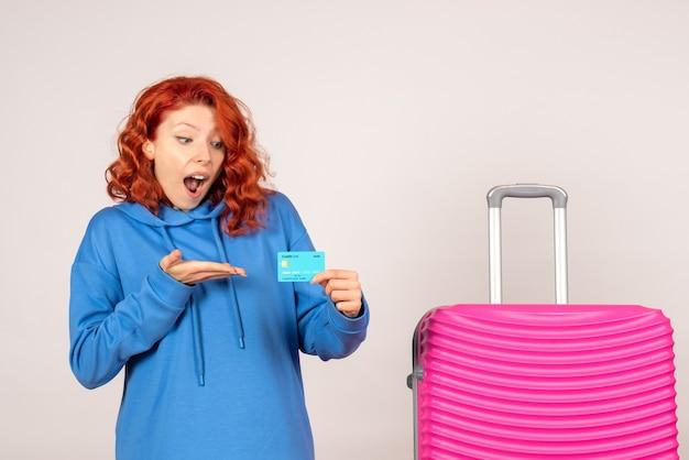 Vorderansicht des weiblichen touristen mit rosa tasche auf weißer wand