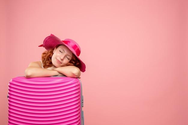 Vorderansicht des weiblichen touristen mit rosa tasche, die auf rosa wand schläft
