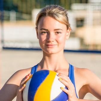 Vorderansicht des weiblichen volleyballspielers auf dem strand, der ball hält
