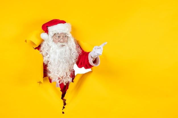 Vorderansicht des weihnachtsmannes, der durch zerrissene gelbe papierwand schaut