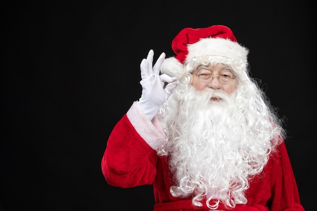 Vorderansicht des weihnachtsmannes im klassischen roten anzug mit weißem bart an der schwarzen wand
