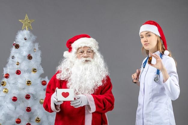 Vorderansicht des weihnachtsmannes mit ärztin, die kleine dose mit pillen auf grauer wand hält