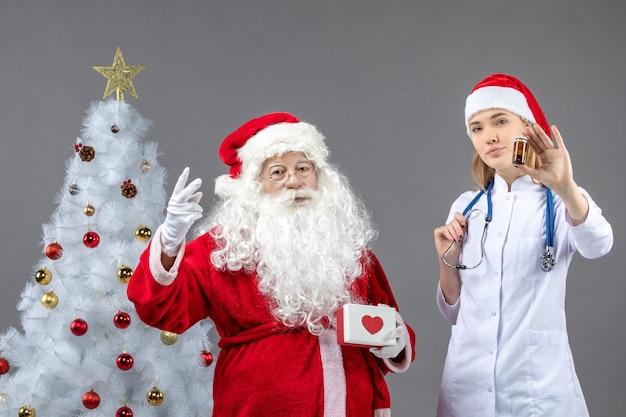 Vorderansicht des weihnachtsmannes mit ärztin, die kleine flasche mit pillen auf grauer wand hält