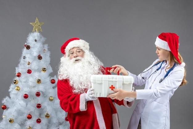 Vorderansicht des weihnachtsmannes mit ärztin, die von ihm erste-hilfe-kasten an der grauen wand nimmt