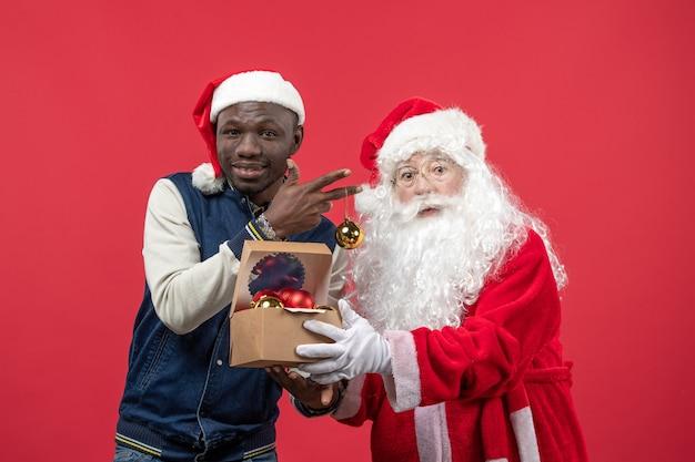Vorderansicht des weihnachtsmannes mit dem jungen jungen mann, der weihnachtsbaumspielzeug an der roten wand hält