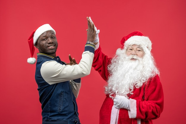 Vorderansicht des weihnachtsmannes mit dem jungen mann an der roten wand