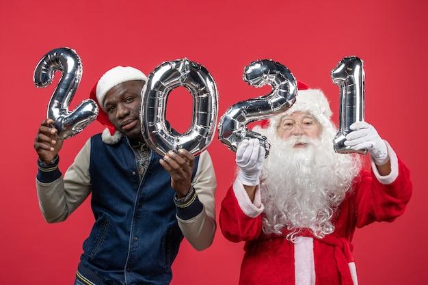 Vorderansicht des weihnachtsmannes mit dem jungen mann, der schrift auf roter wand hält