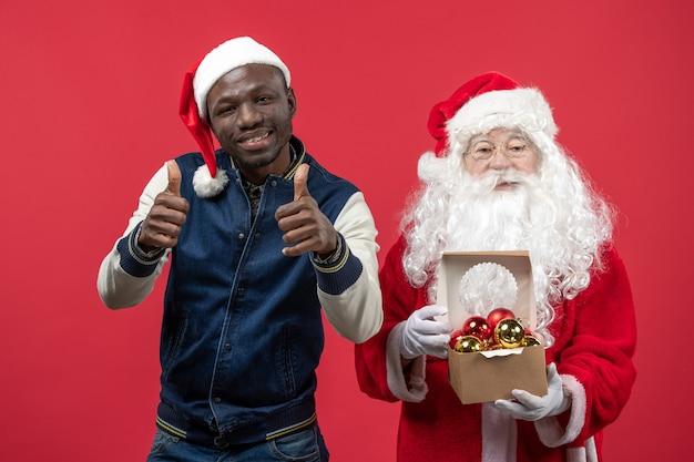 Vorderansicht des weihnachtsmannes mit dem jungen mann, der weihnachtsbaumspielzeug an der roten wand hält