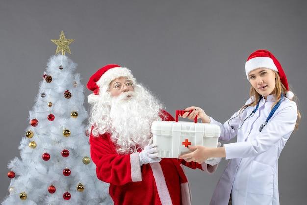 Vorderansicht des weihnachtsmannes mit der ärztin, die von ihm erste-hilfe-kasten auf einer grauen wand nimmt