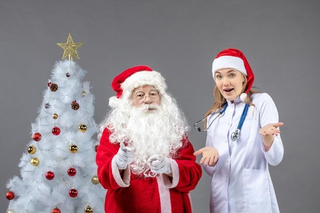 Vorderansicht des weihnachtsmannes mit der jungen ärztin auf einer grauen wand