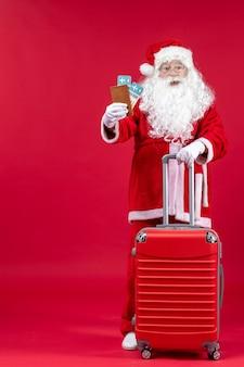 Vorderansicht des weihnachtsmannes mit der tasche, die tickets hält und sich auf die reise an der roten wand vorbereitet
