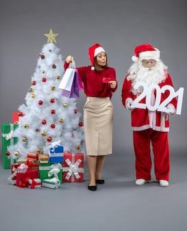Vorderansicht des weihnachtsmannes mit frau, die einkaufstaschen und 2021 zeichen auf grauer wand hält