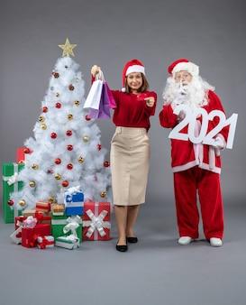Vorderansicht des weihnachtsmannes mit frau, die einkaufstaschen und bankkarte an der grauen wand hält