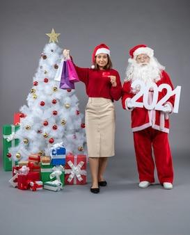 Vorderansicht des weihnachtsmannes mit frau, die einkaufstaschen und banner 2021 auf grauer wand hält