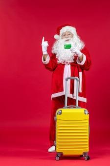 Vorderansicht des weihnachtsmannes mit gelbem beutel, der grüne bankkarte an der roten wand hält