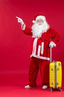Vorderansicht des weihnachtsmannes mit gelbem beutel, der reise für rote wand vorbereitet