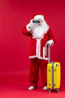 Vorderansicht des weihnachtsmannes mit gelber tasche, die foto mit kamera an der roten wand nimmt