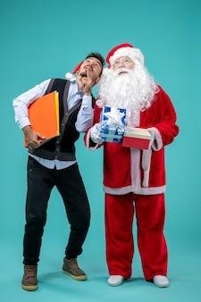 Vorderansicht des weihnachtsmannes mit jungem mann und präsentiert auf blauer wand
