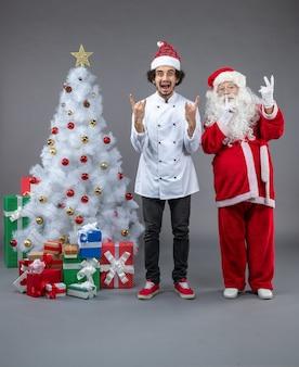 Vorderansicht des weihnachtsmannes mit männlichem koch um weihnachtsgeschenke auf grauer wand