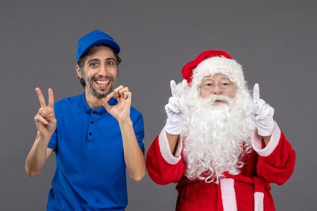 Vorderansicht des weihnachtsmannes mit männlichem kurier an der grauen wand