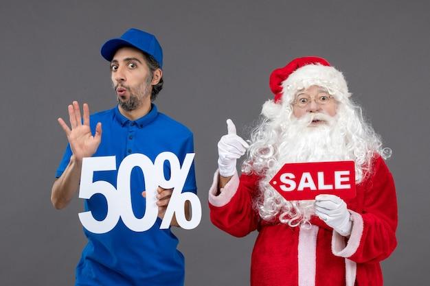 Vorderansicht des weihnachtsmannes mit männlichem kurier, der 50% und verkaufsfahnen auf grauer wand hält