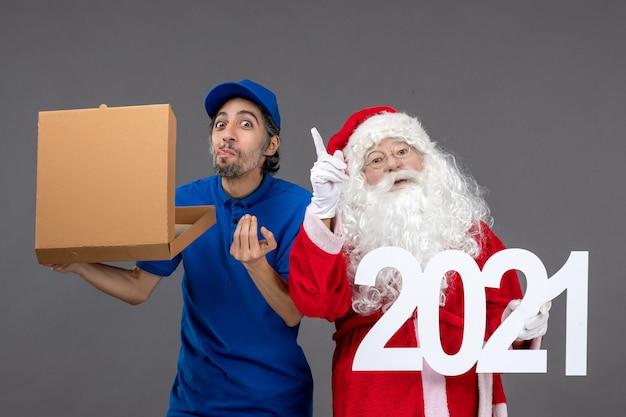Vorderansicht des weihnachtsmannes mit männlichem kurier, der einkaufstaschen und nahrungsmittelkasten an der grauen wand hält