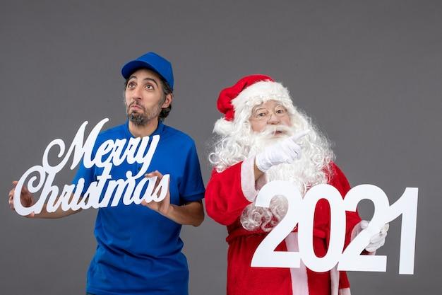 Vorderansicht des weihnachtsmannes mit männlichem kurier, der frohe weihnachten und 2021 bretter an der grauen wand hält