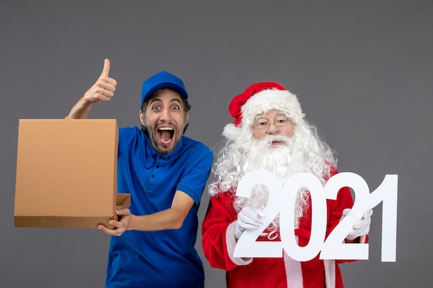 Vorderansicht des weihnachtsmannes mit männlichem kurier, der nahrungsmittelbox hält und auf die graue wand schreibt