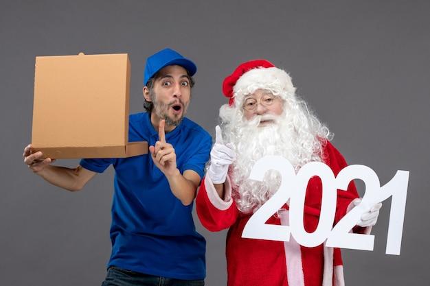 Vorderansicht des weihnachtsmannes mit männlichem kurier, der nahrungsmittelbox und an der grauen wand hält