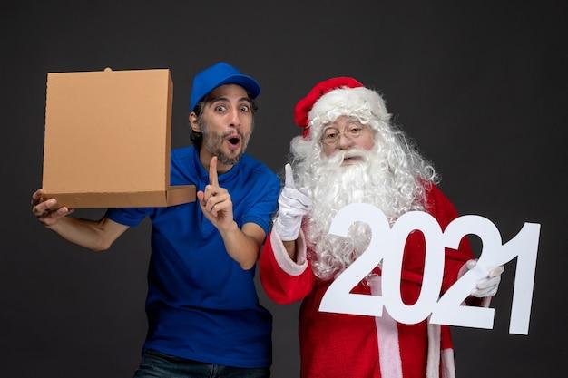 Vorderansicht des weihnachtsmannes mit männlichem kurier, der nahrungsmittelbox und auf dunkler wand hält