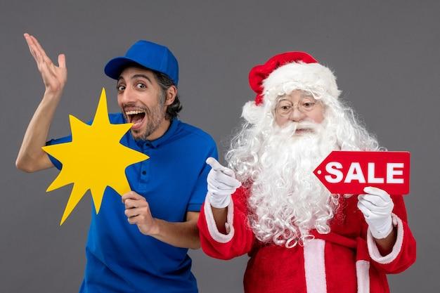 Vorderansicht des weihnachtsmannes mit männlichem kurier, der verkaufsfahne und gelbes zeichen an der grauen wand hält