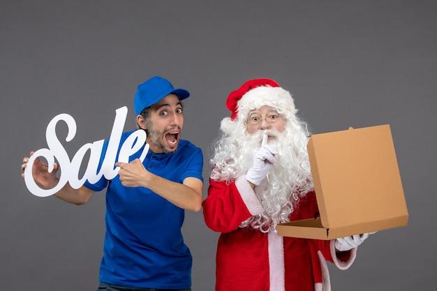 Vorderansicht des weihnachtsmannes mit männlichem kurier, der verkaufsfahne und nahrungsmittelbox auf der grauen wand hält