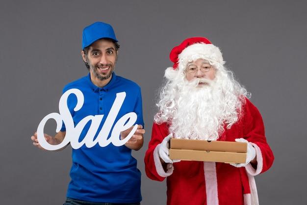 Vorderansicht des weihnachtsmannes mit männlichem kurier, der verkaufsfahne und nahrungsmittelkästen an der grauen wand hält