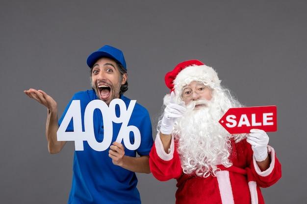 Vorderansicht des weihnachtsmannes mit männlichem kurier, der verkaufsfahnen an der grauen wand hält