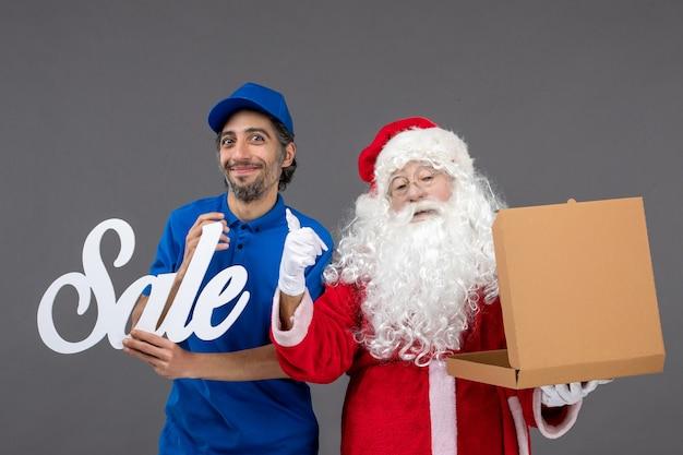 Vorderansicht des weihnachtsmannes mit männlichem kurier, der verkaufsschreiben und leere nahrungsmittelbox auf der grauen wand hält
