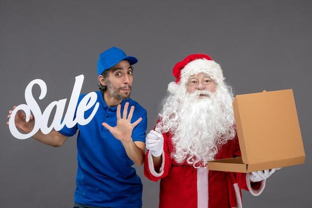 Vorderansicht des weihnachtsmannes mit männlichem kurier, der verkaufsschreiben und nahrungsmittelbox auf grauer wand hält