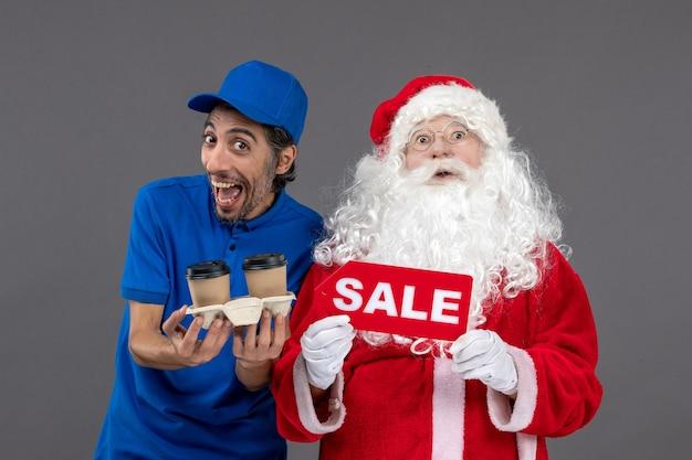 Vorderansicht des weihnachtsmannes mit männlichem kurier, der verkaufsschrift und kaffee an der grauen wand hält