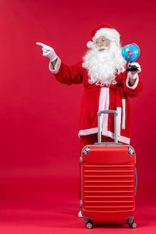 Vorderansicht des weihnachtsmannes mit tasche, die kleinen globus hält und sich auf reise auf roter wand vorbereitet